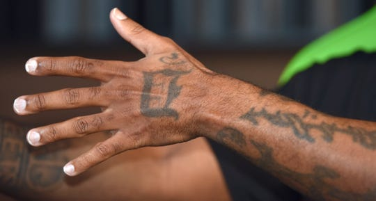 "Royce da 5'9"" expresses with an English D on the back of his left hand."