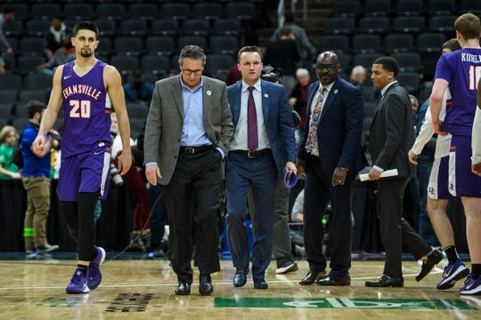 Evansville's Sam Cunliffe (20), from left, Head Coach Todd Lickliter and Assistant Coaches Logan Baumann, Bennie Seltzer, and Terrence Commodore walk off the court following their 58-55 loss to the Valparaiso Crusaders in the first round of the Missouri Valley Conference Tournament at the Enterprise Center in St. Louis, Ill., Thursday, March 5, 2020.