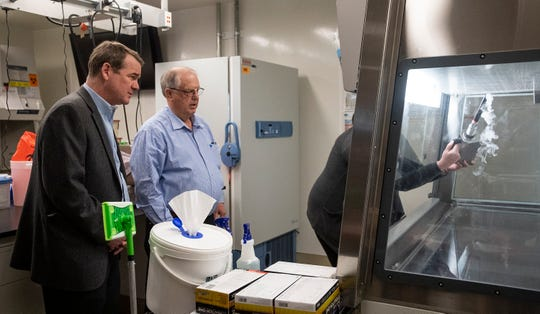Senator Michael Bennet, left, watches a demonstration in the biocontainment lab with Robert Ellis, the Colorado State University Biosafety Director, at the Colorado State University Infectious Disease Research Lab in Fort Collins, Colo. on Friday, March 6, 2020. Scientists are currently working on a coronavirus vaccine at the CSU Infectious Disease Research Center.