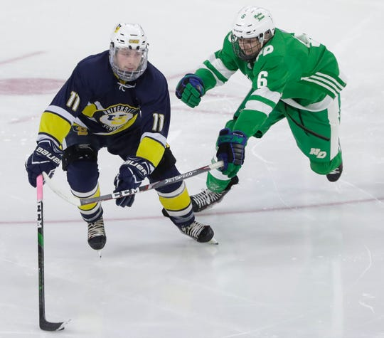 Green Bay Notre Dame's Eli Canadeo (6) tries to poke the puck away from University School of Milwaukee's Tyler Herzberg (11) during a WIAA Division 1 state semifinal Friday at the Alliant Energy Center in Madison.