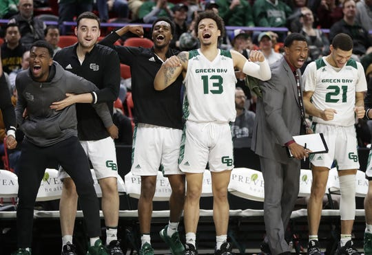 UWGB men's basketball players and staff cheer from the sidelines during the second half of a Horizon League tournament quarterfinal against Oakland on Thursday. The Phoenix defeated the Golden Grizzlies 78-63.