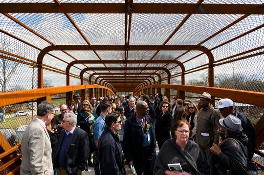 Southernside community members walk across the Hampton Avenue Bridge during a dedication event Friday, March 6, 2020.