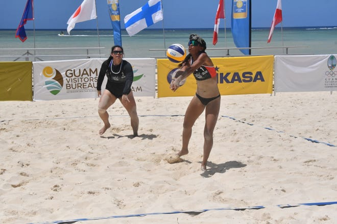Kendra Byrd, right, tiptoes to pass a high serve to her partner, Kara Eugenio, during their match against a U.S. team March 6 at Jimmy Dee's Paradise Beach Resort & Bar in Tamuning in the Guam Beach Cup 2020. The top-seeded Guam team lost 21-4, 21-5.