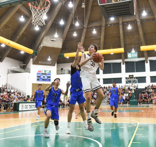 Father Duenas' Matthew Fegurgur (35) attempts to score on a fast break against the Saint Paul Warriors during the IIAAG Boys Basketball championship game at the University of Guam Calvo Field House in Mangilao, March 6, 2020. Fegurgur lead his team with 12 points in a championship win.