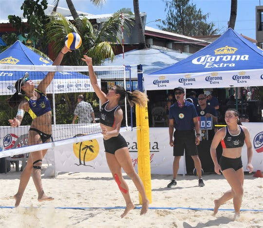 Hallie Wigsten, center, gets her spike blocked by an opponent from Japan on Friday in the Guam Beach cup 2020 at Jimmy Dee's Paradise Beach Resort & Bar in Tamuning.