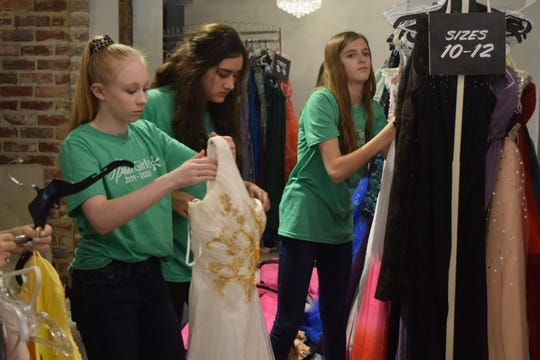 From left, Abigail Dorgan, Alice Pennebaker and Sophie Boover hang dresses on a rack at Bliss Bridal in Hattiesburg, Miss., Thursday, March 5, 2020. Dresses in all sizes will be available Sunday at Bliss during Forrest General Spirit Girls' annual Prom-A-Palooza, where girls can rent dresses for $12 instead of buying expensive gowns.
