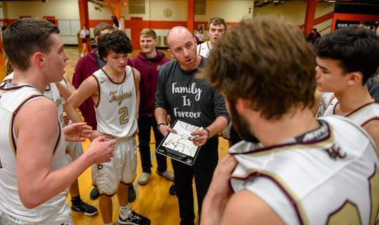 Webster County head coach Jon E. Newton talks to his team during a second quarter timeout as the Webster County Trojans play the University Heights Blazers in the Boys Second Region Tournament at Hopkinsville High School Thursday, March 5, 2020.