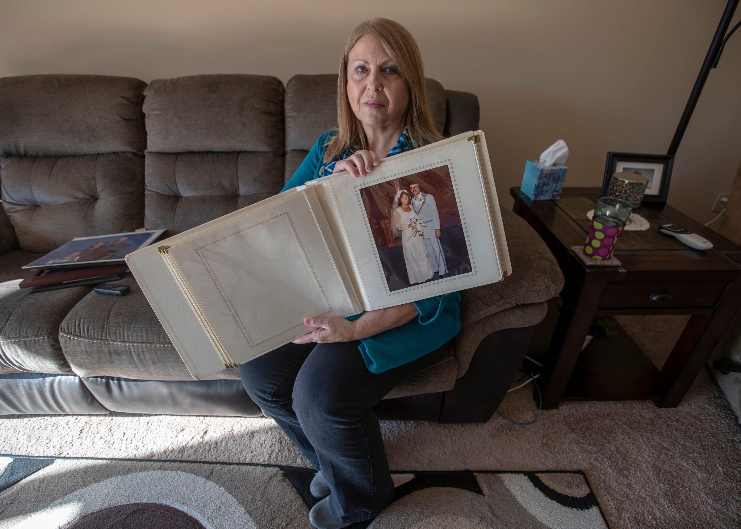 Cathy King holds an album of wedding pictures with her husband, Greg Robinson, on Dec. 4, 2019. Robinson died in 2015 after complications that allegedly arose from improper care.