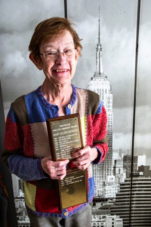 Mary Ellen Chudacek poses for a photo while holding a plaque with shows she directed for the Iowa City Community Theatre, Wednesday, March 4, 2020, at her home in Iowa City, Iowa.