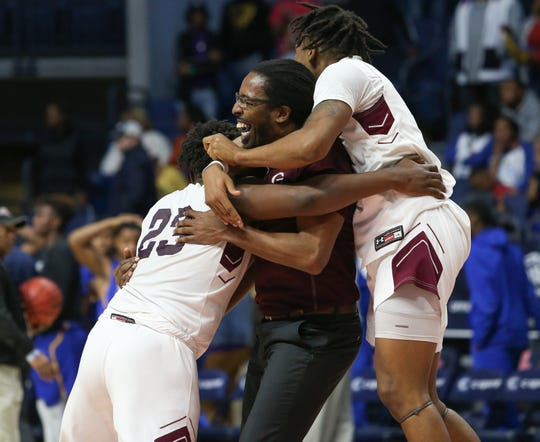 Greenwood head basketball coach Fredric Ford is hugged by players following the overtime win in the 2020 MHSAA Basketball Class 4A Championship at the Pavilion at Ole Miss on Thursday, March 5, 2020.