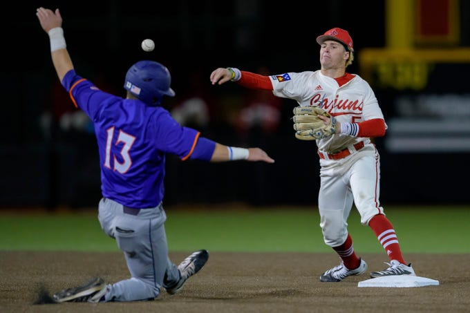 Louisiana Lafayette second baseman Hayden Cantrelle tries to complete a double play after forcing out Northwestern St. catcher Marshall Skinner during an NCAA baseball game on Wednesday, Feb. 26, 2020, in Lafayette, La. (AP Photo/Matthew Hinton)