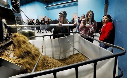 Shannon Busher of Combustion Brewing Pickerington uses a hoe to remove spent grain from the mash tun at Outerbelt Brewing while Betsy Rutter of Double Edge Brewing Lancaster and and Elena Taylor of Loose Rail Canal Winchester look on March 5, 2020. Outerbelt Brewing in Carroll was holding a Women's Brew Day to help diversity in the industry and network for those individuals already working in the craft beer industry. [Eric Albrecht/Dispatch]
