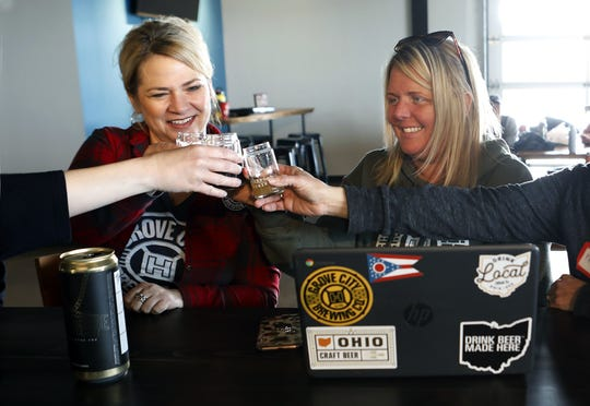 Jodi Burroughs and Naomi Jackson of Grove City Brewing toast with others March 5, 2020. Outerbelt Brewing was holding a Women's Brew Day to help diversity in the industry and network for those individuals already working in the craft beer industry. [Eric Albrecht/Dispatch]
