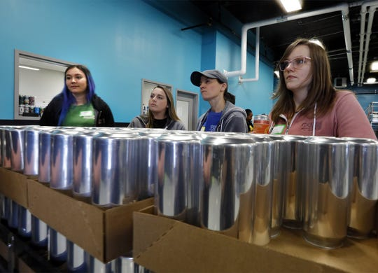 LtoR Andrea Wertz of Nocterra Brewing Company Powell , Devon Taylor , Starr Jinkens and Betsy Rutter all of  Double Edge Brewing Company Lancaster listen to Dominic Kirchgessner of Outerbelt Brewing talk about the canning line at Outerbelt Brewing March 5, 2020. Outerbelt Brewing was holding a Women's Brew Day to help diversity in the industry and network for those individuals already working in the craft beer industry. [Eric Albrecht/Dispatch]