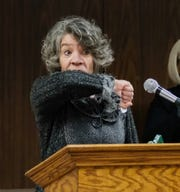 Linda Vail, Ingham County health officer, demonstrates how people should cough into the  elbow at a news conference concerning the COVID-19, or coronavirus, Friday, March 6, 2020.