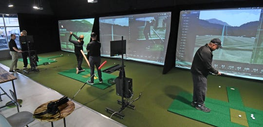 Multiple screens project images simulating a golf course at 419 Golf on August Drive in Ontario.