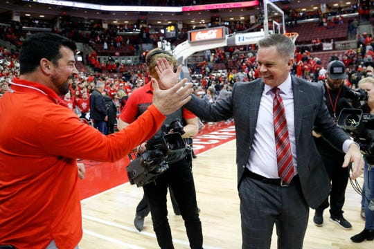 Ohio State football coach Ryan Day congratulates basketball coach Chris Holtmann as he leaves the court after a recent home win over Michigan.