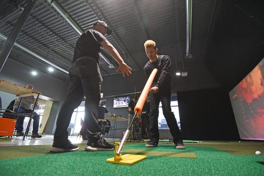 Tyler Deskins instructs Gavin Auck on his swing Friday afternoon at 419 Golf.