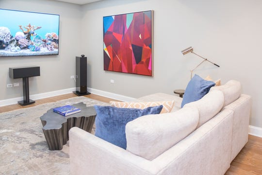 A large-screen TV and surround-sound system offer optimal movie watching in  the media room.
