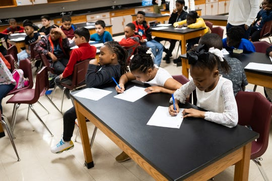 Students write questions and take notes during Kat Gordon's talk as part of A Diamond in the Rough at Dexter Elementary, Thursday, March 6, 2020, in Memphis, Tenn.
