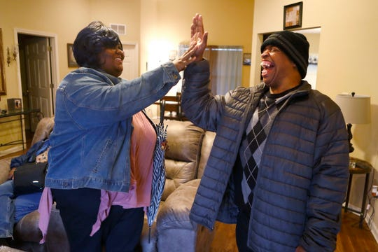 Shakelia Funches, an employee for SRVS, shares a high-five with Victor Griffin from his independent living home on Thursday, Feb. 20, 2020. Funches cares for developmentally challenged adults, including Griffin, with services such as bathing, cleaning and cooking for, monitoring medications and engaging in community activities with, for around ten dollars per hour. The pay, which is stipulated by state government, causes her to take on extended overtime hours to make ends meet. Across Tennessee, groups of direct support professionals are joining together to advocate for raising the average minimum wage for their profession.