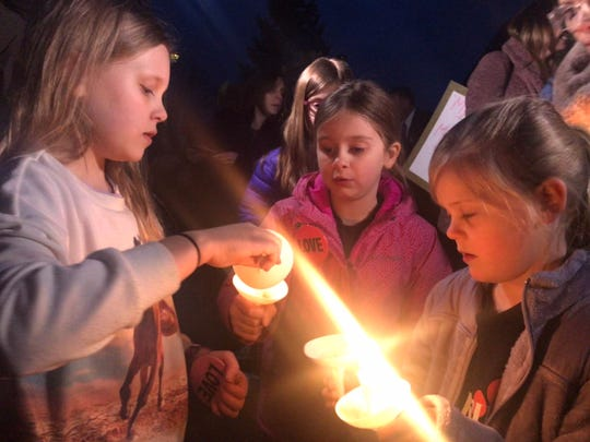 Ten-year-old Noelle May lights a vigil candle for Lucia Wheeler, 7, while Remi May, 6, looks on at a rally March 5 in front of Cedarburg City Hall to support a family who received a racist letter.