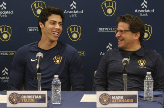 Brewers outfielder and principal owner Mark Attanasio share a laugh during a news conference Friday announcing Yelich's new contract.