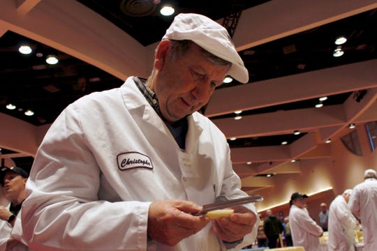 Judge Christophe Megevand inspects a piece of Gruyere cheese  at the biennial World Championship Cheese Contest on Tuesday at the Monona Terrace Convention Center in Madison. It's the largest technical cheese, butter and yogurt competition in the world.