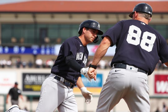 Mar 5, 2020; Lakeland, Florida, USA;  New York Yankees catcher Kyle Higashioka (66) is congratulated by third base coach Phil Nevin (88) after hitting a home run during the fourth inning against the Detroit Tigers  at Publix Field at Joker Marchant Stadium.