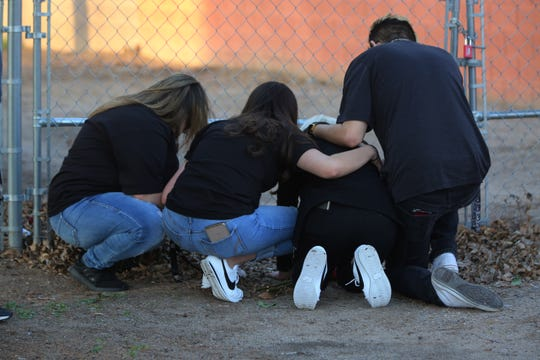 Antonio Valenzuela's daughters, flanked by friends, kneel Thursday March 5, 2020, at the spot their father died during an altercation police on Feb. 29, 2020. Valenzuela was 40.