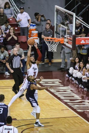 NMSU junior Johnny McCants (35) jumps to dunk as the New Mexico State Aggies face off against the Cal Baptist Lancers at the Pan American Center in Las Cruces on Thursday, March 5, 2020.