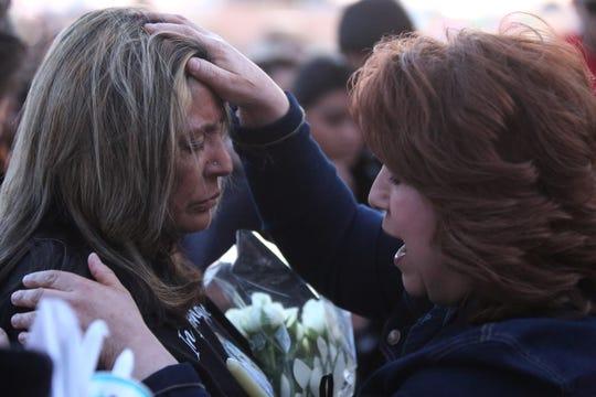 Pricilla Hernandez prays for Antonio Valenzuela's mother, Rosalie Valenzuela, during a candlelight vigil in Antonio's honor on Thursday March 5, 2020.