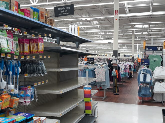 """The shelves beneath a sign reading """"Disinfecting Wipes"""" are bare at the Walmart Supercenter on Walton Boulevard on Thursday, March 5, 2020."""
