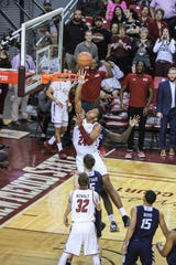 NMSU freshman William McNair (24) jumps to tip the ball in as the New Mexico State Aggies face off against the Cal Baptist Lancers at the Pan American Center in Las Cruces on Thursday, March 5, 2020.
