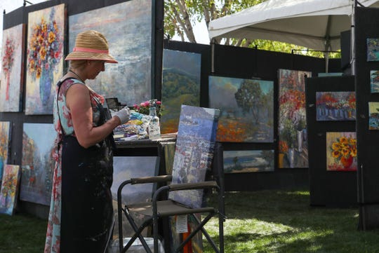 Artist Delia Bradford paints at her booth during the La Quinta Art Celebration, March 5, 2020.