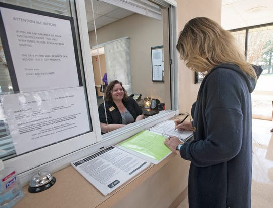 Employee Helen Herndon looks on Friday as a visitor fills out a coronavirus/travel questionnaire before visiting the Sandy Ridge Health and Rehabilitation Center in Milton.