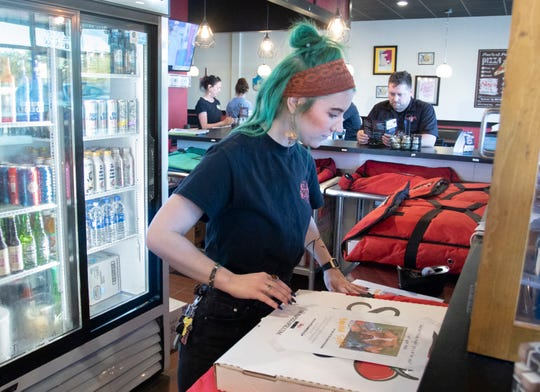 Anna Monk tapes a Friends of the Escambia County Animal Shelter flyer featuring an animal available for adoption on a box at Sky's Pizza Pie in Pensacola on Friday.