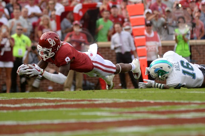Sep 16, 2017; Norman, OK, USA; Oklahoma Sooners wide receiver CeeDee Lamb (9) breaks a tackle attempt by Tulane Green Wave safety P.J. Hall (16) to score a touchdown during the first quarter at Gaylord Family - Oklahoma Memorial Stadium. Mandatory Credit: Mark D. Smith-USA TODAY Sports