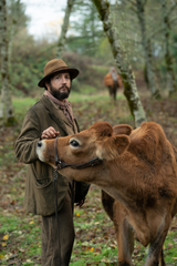 John Magaro as Cookie, along with Evie the cow, in 'First Cow.'