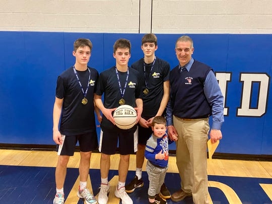 Pine Plains coach Les Funk poses with his nephews Tyler and Adam and his son, Zach Funk, after winning the Section 9 Class C boys basketball championship on Thursday.