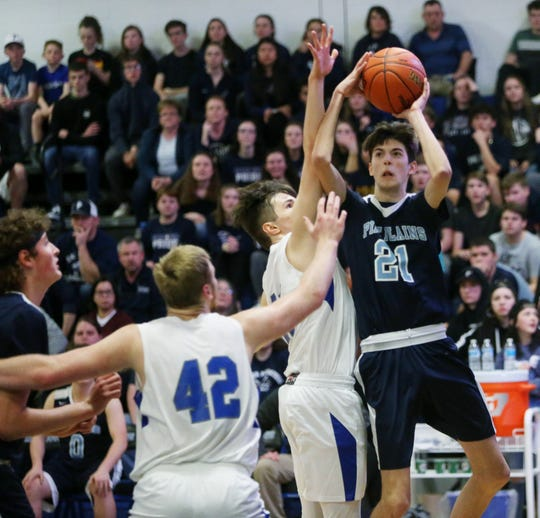 Pine Plains' Zach Funk takes a jump shot over Millbrook's David King during the Section 9 boys basketball championship in Middletown on March 5, 2020.