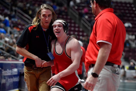 Susquehannock's Colby Romjue is congratulated by his coach, Aaron Trimpey, after winning a first-round PIAA Class 3-A first-round match on Thursday. Romjue would finish eighth in the state at 160.