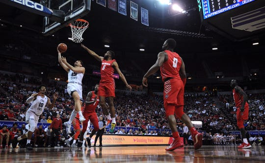 Utah State Aggies guard Abel Porter (15) goes to the basket ahead of New Mexico Lobos guard JaQuan Lyle (5) during the second half of a Mountain West Conference tournament game at Thomas Mack Center.