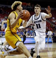 Wyoming's Hunter Maldonado (24) looks to pass as Nevada's Kane Milling (11) defends during the second half of a Mountain West Conference tournament NCAA college basketball game, Thursday, March 5, 2020, in Las Vegas. Wyoming defeated Nevada 74-71.