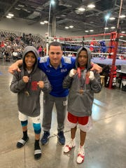 Coach Tim Nolan, center, with two of his young fighters, Javier Mitchell, left, ranked No. 1 in USA at 85 pounds, and Fynest Cummings. Both boxers took home titles at eastern United States qualifier.