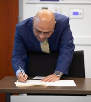 Oscar Moreno Gilson signs his contract to become the Woodburn School District Superintendent during a special school board meeting held March 5, 2020.