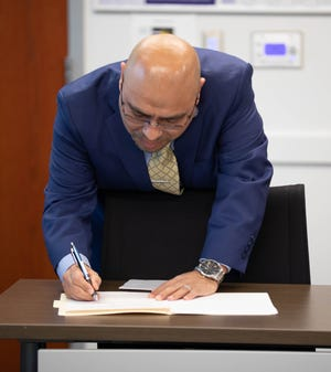 Oscar Moreno Gilson signs his contract to become the Woodburn School District Superintendent during a special school board meeting held on March 5, 2020.