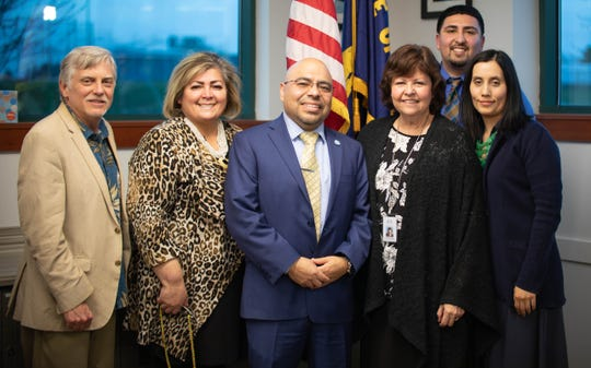 Oscar Moreno Gilson poses for a picture with Woodburn School District School Board members after signing the contract for the district Superintendent position during a special school board meeting March 5, 2020.