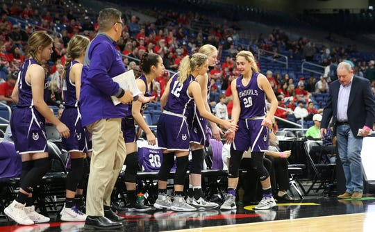 Mason High School's Tristin Keller is consoled by her teammates after fouling out in the fourth quarter against Muenster in a Class 2A girls basketball state semifinal at the Alamodome in San Antonio on Friday, March 6, 2020. Cowgirls head coach Jeff Guice is on the far right.