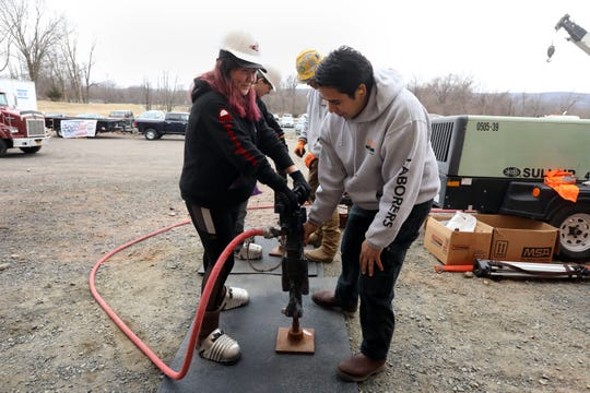 Jenny Perez, a sophomore at Rochembeau Alternative High School in White Plains, uses a jack hammer with the help of Raul Abalos of Laborers Local 60 at the the 21st Construction Career Day hosted by the Construction Industry Council of Westchester and Hudson Valley Inc. March 6, 2020 at Rockland Community College in Suffern.